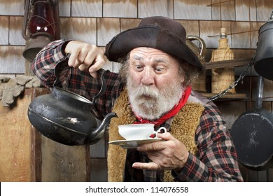 Classic Old West style cowboy cook with felt hat, grey whiskers, red bandanna. He is ready to pour tea into a white china tea cup.