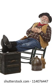 Classic old west style friendly cowboy with felt hat, grey whiskers, revolver. He leans back in a rocking chair with feet up. Isolated on white, vertical, copy space.
