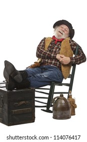 Classic old west style laughing cowboy with felt hat, grey whiskers, revolver. He leans back in a rocking chair with feet up. Isolated on white, vertical, copy space.