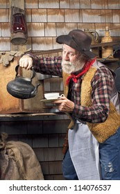 Classic old western style cowboy cook with felt hat, grey whiskers, apron. He is ready to pour tea into a white china tea cup.
