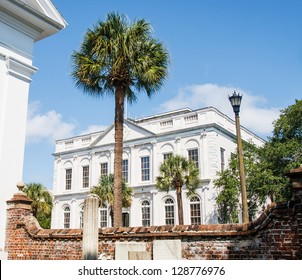 A classic old, white, marble government building beyond a brick wall and palm tree