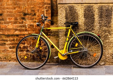 Classic old yellow bicycle on the street.