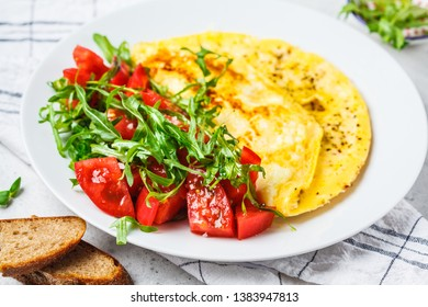 Classic omelet with cheese and tomatoes salad on a white plate.