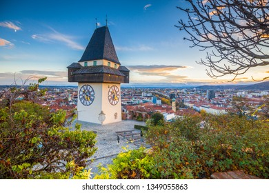 Classic panorama view of the historic city of Graz with famous Grazer Uhrturm clock tower in beautiful evening light at sunset, Styria, Austria