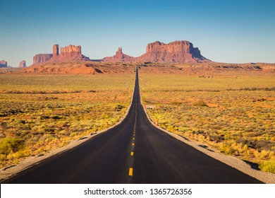 Classic panorama view of historic U.S. Route 163 highway running through famous Monument Valley in beautiful golden evening light at sunset in summer, Utah, western USA