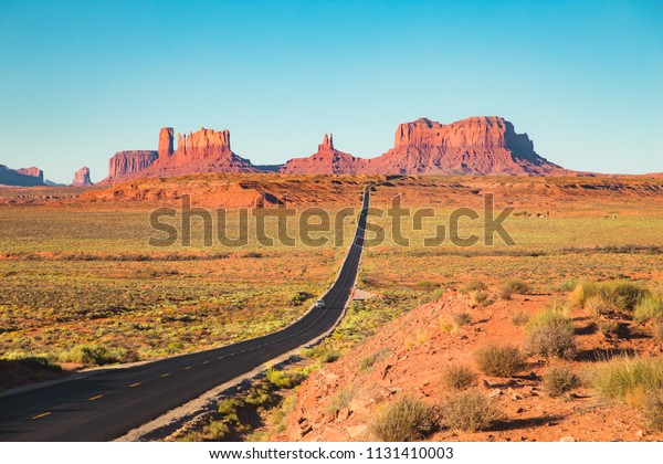 Classic panorama view of historic U.S. Route 163 running through famous Monument Valley in beautiful golden evening light at sunset in summer, Utah, USA