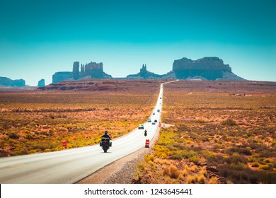 Classic panorama view of motorcyclist on historic U.S. Route 163 running through famous Monument Valley in beautiful golden evening light at sunset in summer, Utah, USA