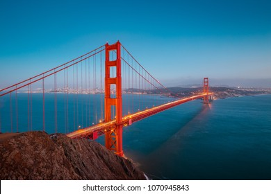 Classic panoramic view of famous Golden Gate Bridge seen from Battery Spencer viewpoint in beautiful post sunset twilight during blue hour at dusk in summer, San Francisco, California, USA