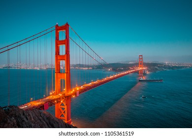 Classic panoramic view of famous Golden Gate with cargo freight ship in beautiful post sunset twilight during blue hour at dusk in summer, San Francisco, California, USA