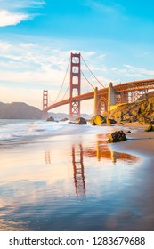 Classic panoramic view of famous Golden Gate Bridge seen from scenic Baker Beach in beautiful golden evening light on a sunny day with blue sky and clouds in summer, San Francisco, California, USA