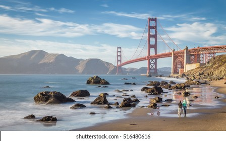 Classic panoramic view of famous Golden Gate Bridge seen from Baker Beach in beautiful evening light on a sunny day with blue sky and clouds in summer, San Francisco, California, USA