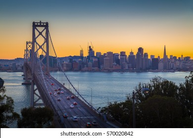 Classic panoramic view of famous Oakland Bay Bridge with the skyline of San Francisco illuminated in beautiful twilight with golden sunset glow in summer, San Francisco Bay Area, California, USA