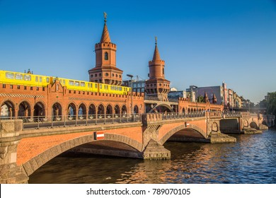 Classic panoramic view of famous Oberbaum Bridge with historic Berliner U-Bahn crossing the Spree river on a beautiful sunny day with blue sky in summer, Berlin, Germany