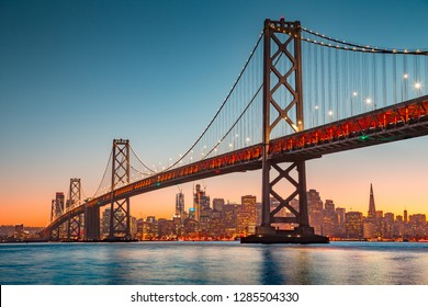 Classic panoramic view of San Francisco skyline with famous Oakland Bay Bridge illuminated in beautiful golden evening light at sunset in summer, San Francisco Bay Area, California, USA - Shutterstock ID 1285504330