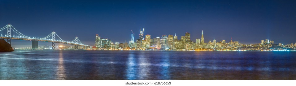 Classic panoramic view of the skyline of San Francisco with famous Oakland Bay Bridge  illuminated in beautiful twilight after sunset in summer, California, USA