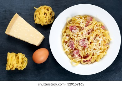 Classic Pasta carbonara Italian. decorated with tangliatelle spaghetti, egg and Parmesan Cheese on blue background