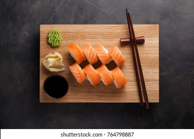 A classic Philadelphia roll with wasabi, ginger and soy sauce on a wooden Board. Salmon, Philadelphia cheese, cucumber, avocado. Japanese sushi on a dark stone background. Top view.
