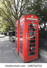 A Classic phonebooth in London, Great Britain outside a park with black fence. Taken in the summer, in the shade. A symbol of United kingdom. Designed by Sir Giles Gilbert 1935. Public telephone