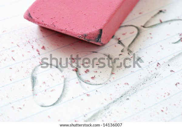 Classic pink eraser on paper with partially erased word - 'oops'.  Macro with extremely shallow dof.  Selective focus on edge of eraser.