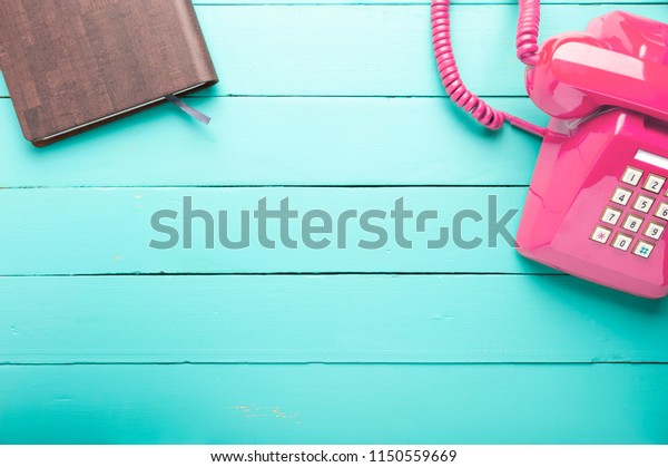 Classic pink telephone receiver with notebook, waiting phone call, Retro telephone and book on old green wooden floor.