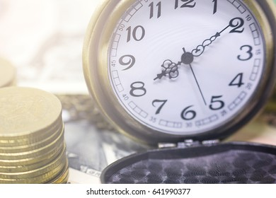 classic pocket watch and coins on dollar banknote, concept and idea of time value and money, business and finance concepts.