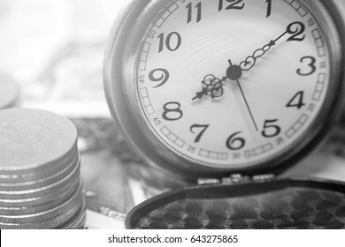 classic pocket watch and coins on dollar banknote, concept and idea of time value and money, business and finance concepts, black and white style