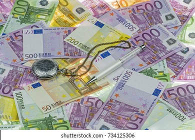 Classic pocket watch and luxurious white-pearl pen on Euro currency (EUR) with 500, 200, 100 and 50 euro bank notes. A concept / idea of time value of money (TVM). Time is money. Euro background