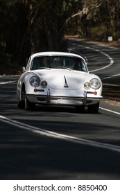 Classic Porsche 356 on tree-lined road