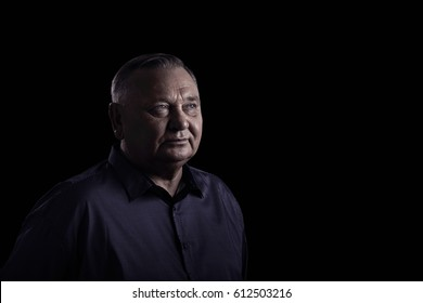 Classic portrait of aged man wearing shirt against black background - retirement concept, copy space