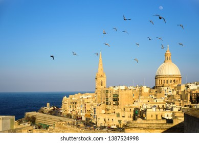 Classic postcard view to Basilica of Our Lady of Mount Carmel and St Paul's Pro-Cathedral. Valletta, Malta. Clear sky, sunshine, flying birds