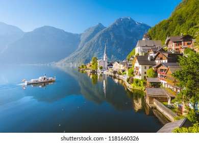 Classic postcard view of famous Hallstatt lakeside town with traditional ship in beautiful morning light at sunrise in summer, Salzkammergut, Austria