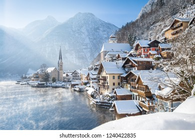 Classic postcard view of famous Hallstatt lakeside town in the Alps on a beautiful cold sunny day with blue sky and clouds at sunrise in winter, Salzkammergut region, Austria