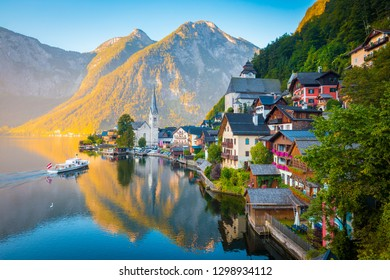 Classic postcard view of famous Hallstatt lakeside town in the Alps with traditional passenger ship in early morning light at sunrise on a beautiful day in summer, Salzkammergut region, Austria