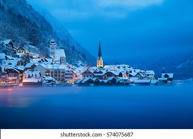 Classic postcard view of famous Hallstatt lakeside town in the Alps in mystic twilight during blue hour at dawn on a beautiful cold and cloudy day with fog in winter, Salzkammergut region, Austria