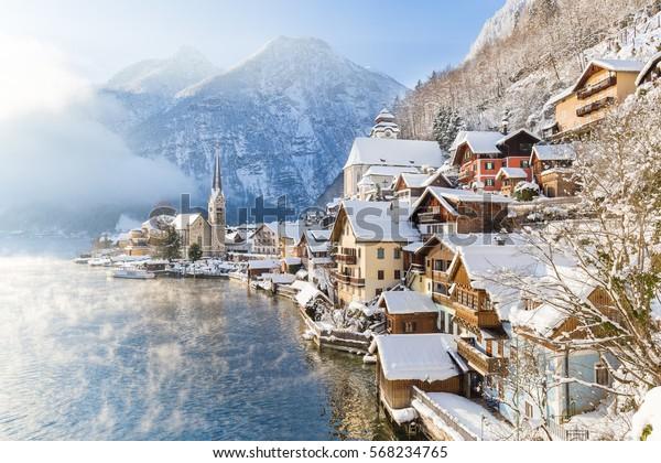Vista postal clásica de la famosa ciudad de Hallstatt junto al lago en los Alpes con barco de pasajeros en un hermoso día frío y soleado con cielo azul y nubes en invierno, región de Salzkammergut, Austria