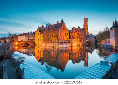 Classic postcard view of the historic city center of Brugge, often referred to as The Venice of the North, with famous Rozenhoedkaai illuminated in beautiful twilight, West Flanders province, Belgium