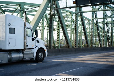 Classic powerful white big rig semi truck with big cab sleeping compartment for long haul routes going on Columbia River Interstate Bridge transporting commercial cargo to point of destination