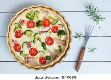Classic quiche lorraine pie with broccoli, cheese and tomatoes in baking dish on white table background. Top view.