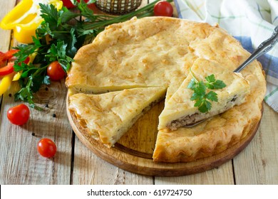 A classic quiche Lorraine pie with potatoes, cabbage, fish and cheese on a wooden table.