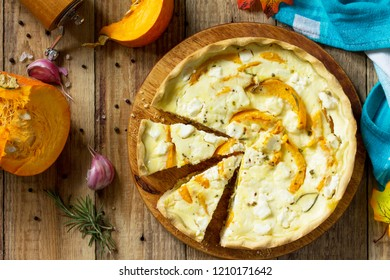 Classic Quiche Lorraine Pie with Pumpkin and Feta Cheese on a wooden table. Top view flat lay background.
