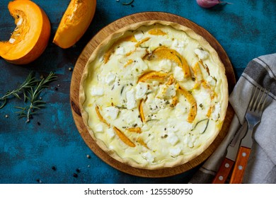 Classic Quiche Lorraine Pie with Pumpkin and Feta Cheese on blue concrete or stone table. Top view flat lay background.