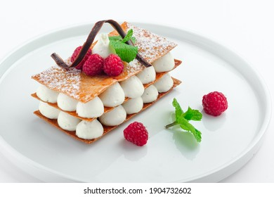 Classic raspberry mille feuille dessert with whipped sour cream on a white plate