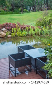 Classic rattan chairs and table on wooden balcony beside the small beautiful lake in a green plant garden,Fujian,China