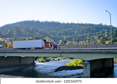 Classic red big rig semi truck with refrigerated semi trailer transporting commercial cargo and moving on the bridge across mountain river in stunning natural Columbia Gorge aria with wooded hills