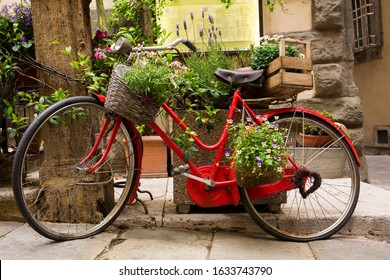 Classic red bike adorned with flowers, basket and wine crate in Cortona, a hill town in the Tuscany region of Italy