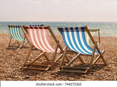 Classic red, blue, green and white striped deckchairs on the beach, the sea in the background in warm evening light