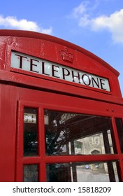 Classic red British telephone booth against blue sky