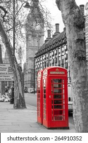 Classic red British telephone boxes with Big Bang in the background. Black and with image with selective red color correction.