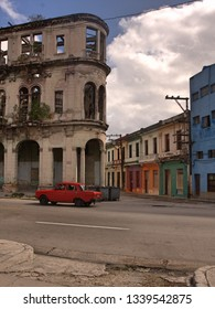 Classic red car in front of abandoned heritage building and facades of colorful rowhouse low-rise buildings and empty road in foreground
