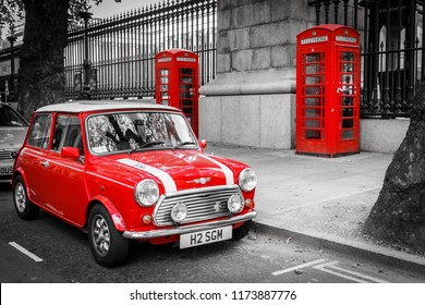 A classic red mini parked in front of two red phone boxes in London